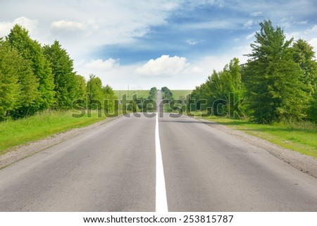 highway among green fields and blue sky - stock photo