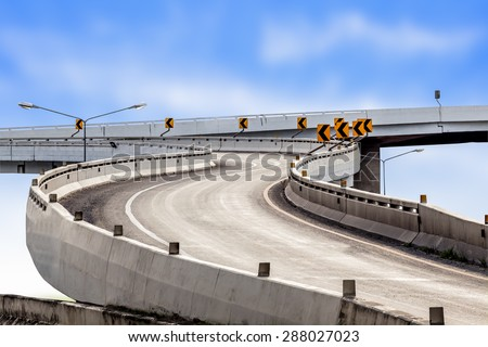Highway asphalt road curve and traffic sign with blue sky background - stock photo