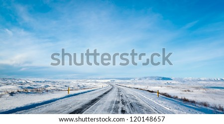 Highway 1 Iceland. Clear road covered in snow and ice under a deep blue sky - stock photo