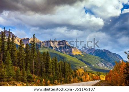 Highway in Banff National Park. Mountains and colorful autumn forest illuminated by the sunset. Canada, Alberta, Rocky Mountains - stock photo