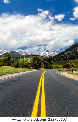 Highway in the rocky mountains national park, blue contrasty sky and mountains peeks snow caped in the distance, lush greens - stock photo