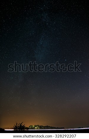 Highway on a background of bright stars of the night sky and the Milky Way. - stock photo