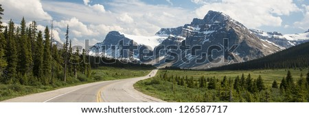 Highway passing below the Canadian Rockies, Banff National Park, Alberta - stock photo