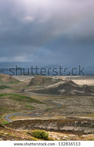 Highway through Iceland landscape at overcast day with rainbow. Vertical shot - stock photo