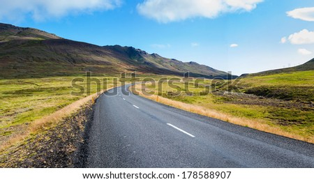 Highway through Iceland landscape at sunny day. Horizontal shot - stock photo