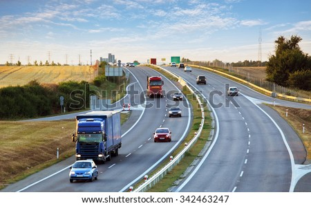 Highway traffic in sunset with cars and trucks - stock photo