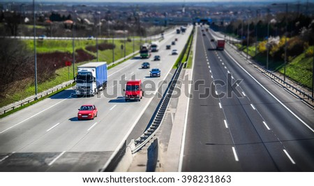 Highway transportation with cars and truck in tiltshift view. - stock photo