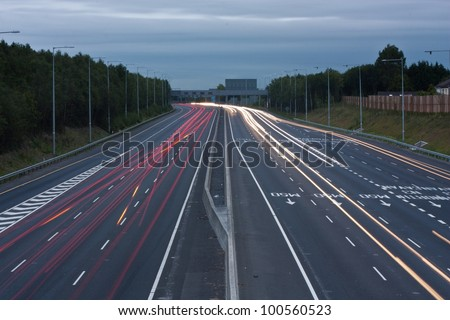 Highway with light trails of passing vehicles - stock photo