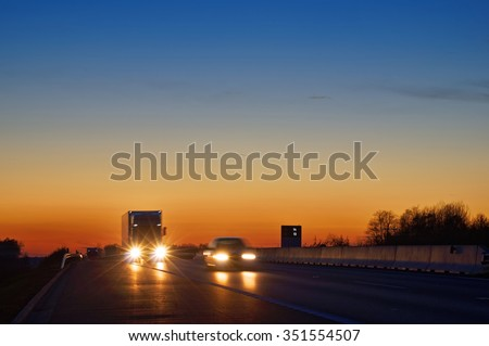 Highway with oncoming trucks and a car after sunset. Shining the spotlight cars. Information boards about the temperature. Blue and orange sky is clear. - stock photo