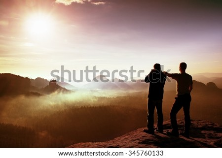 Hiker and photo enthusiast stay on cliff and thinking. Dreamy fogy landscape, blue misty sunrise in a beautiful valley below, soft focus - stock photo