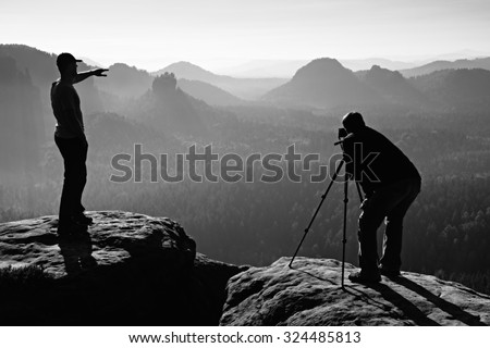 Hiker and photo enthusiast stay with tripod on cliff and thinking. Dreamy fogy landscape, blue misty sunrise in a beautiful valley below. Black and white photo - stock photo