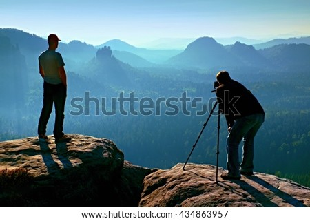 Hiker and photo enthusiast stay with tripod on cliff and thinking. Dreamy fogy landscape, blue misty sunrise in a beautiful valley below - stock photo