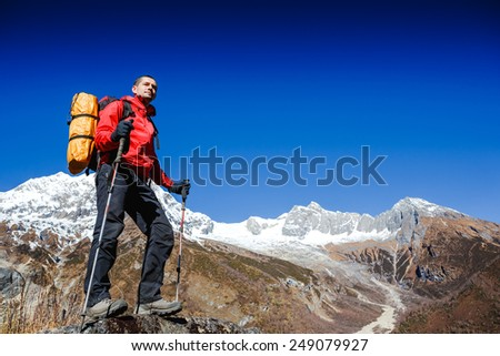 hiker at the top of a rock with backpack enjoy sunny day. Himalayas - stock photo