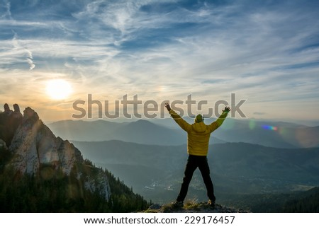 hiker celebrates success in the sunset above the valley - stock photo