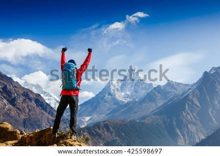 Hiker cheering elated and blissful with arms raised in the sky after hiking. Everest base camp trek - stock photo
