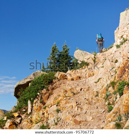 Hiker climbing up a steep trail in the Rocky Mountains in Colorado. - stock photo