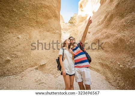 Hiker - Couple of young hikers relaxing in Bryce Canyon smiling togheter indicating a point with his finger. Caucasian group in Bryce Canyon National Park landscape - stock photo