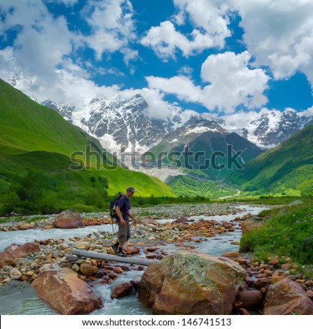 Hiker cross the mountain river - stock photo