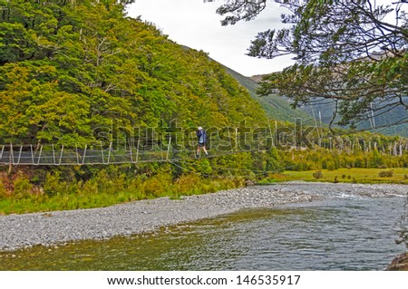 Hiker Crossing the Travers River in New Zealand - stock photo