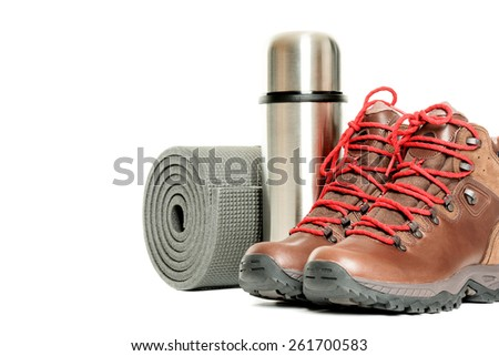 Hiker equipment: pair of mountain boots, thermo flask and sleeping mat on white background - stock photo