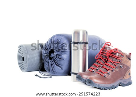 Hiker equipment: pair of mountain boots, thermo flask, sleeping bag and mat on white background - stock photo