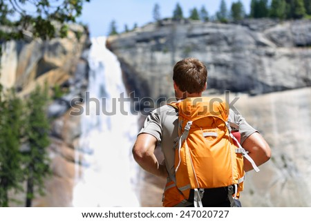 Hiker hiking with backpack looking at waterfall in Yosemite park in beautiful summer nature landscape. Portrait of male adult back standing outdoor. - stock photo
