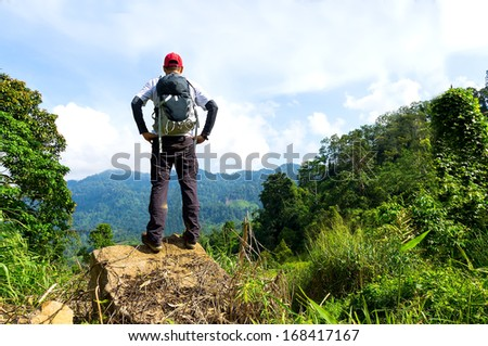 Hiker in a nature green forest at mountain summit - stock photo