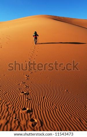 Hiker in sand desert - stock photo