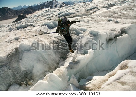 hiker in the mountain. jump through the glacier crevasse. mountaineering - stock photo