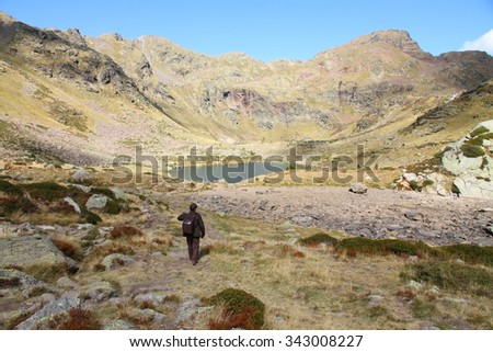 Hiker in Tristaina high mountain lakes in Pyrenees mountains  Andorra - stock photo