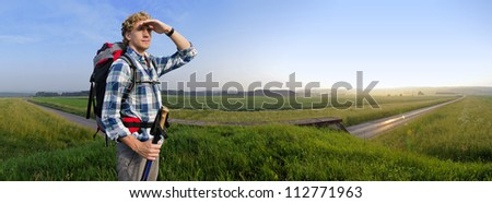 Hiker in vast wheat fields at sunset with a small rural road passing underneath him - stock photo