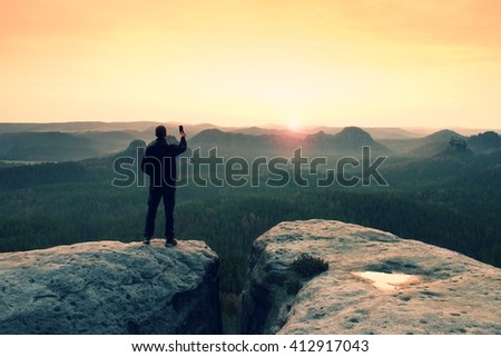 Hiker is taking photo by smart phone on the peak of mountain at sunrise. - stock photo