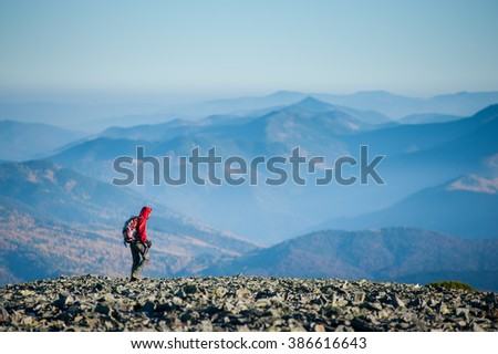 Hiker is walking on the rocky mountain plato on backpacking trip in the evening. Beautiful mountains on background. Rear view. Eco tourism and healthy lifestyle concept. Copy space. - stock photo