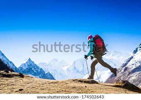 Hiker jumps among Himalayas - stock photo