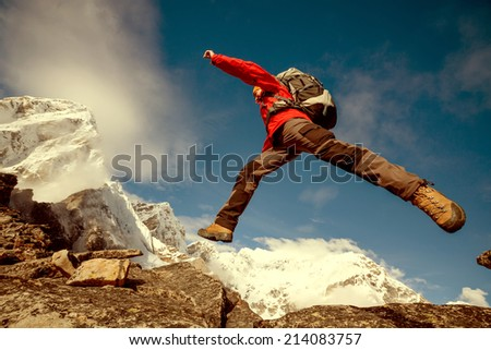 Hiker jumps on the rock near Everest in Nepal - stock photo