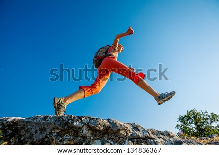 Hiker jumps over the rock - stock photo