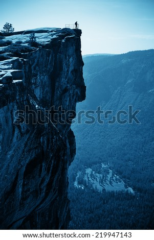 Hiker look down from Taft Point in Yosemite BW. - stock photo
