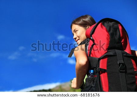 Hiker looking while backpacking / hiking in nature. Copy space on blue sky. - stock photo