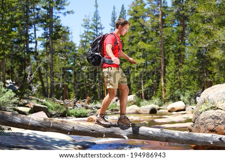 Hiker man hiking crossing river walking in balance on fallen tree trunk in Yosemite landscape nature forest. Happy male hiker trekking outdoors in Yosemite National Park., California, United States. - stock photo