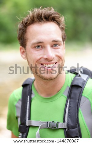 Hiker man portrait of outdoors hiking sporty guy smiling happy at camera wearing backpack outdoors during hike in forest nature. Caucasian male model outside. - stock photo