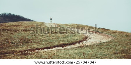 Hiker man walking down on footpath on hill - stock photo