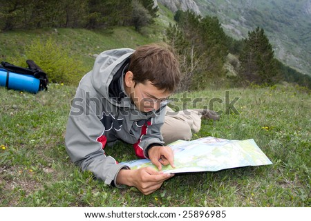 Hiker man with backpack looking to the map - stock photo