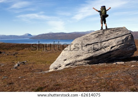 Hiker on a huge stone in lapland - stock photo