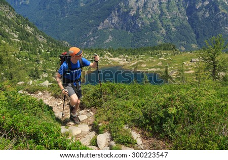 Hiker on a trail near a lake in the mountains of Ticino, Switzerland. - stock photo