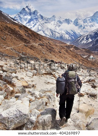 Hiker on Everest Base Camp Trek with Mount Ama Dablam in the background, Sagarmatha National Park, Nepal Himalaya. - stock photo