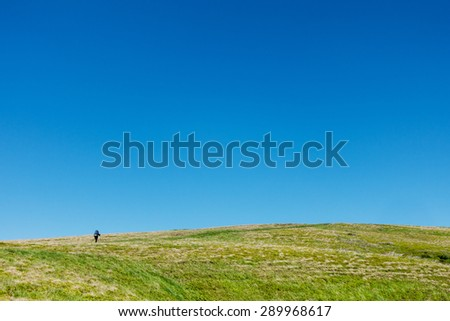 Hiker on the green plain under blue skies - outdoor motive - stock photo