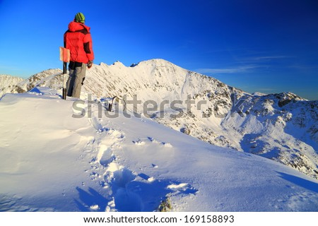 Hiker on top of the mountain, admiring the sunset landscape - stock photo