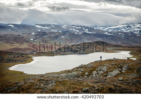 Hiker over a lake in the autumn wilderness of Sweden - stock photo