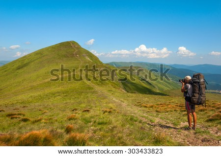 Hiker photographer taking picture of the valley with mountains  - stock photo