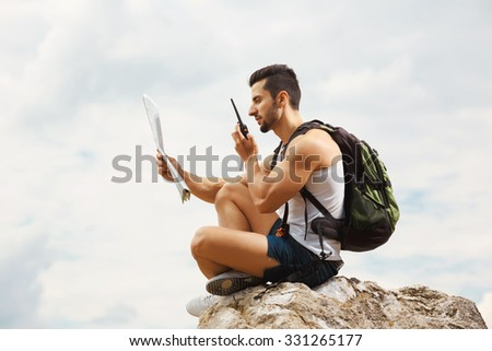 Hiker portrait. Explorer talking via radio station. Young man tourist with a backpack sitting on top of a mountain and holding map - stock photo